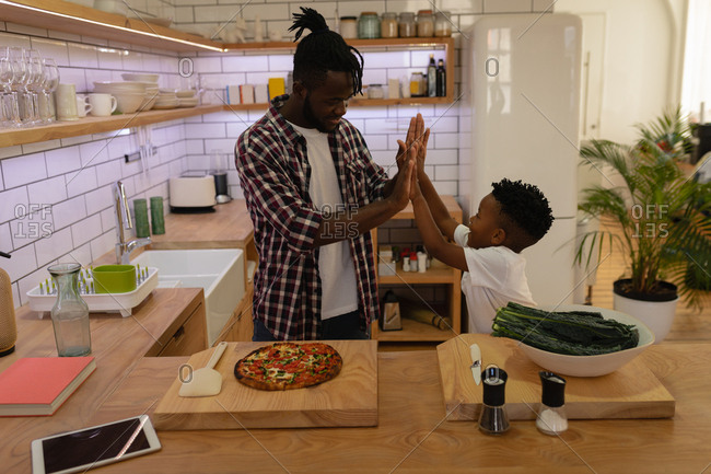 Side view of happy African-American father giving high five to his son while finishing cooking
