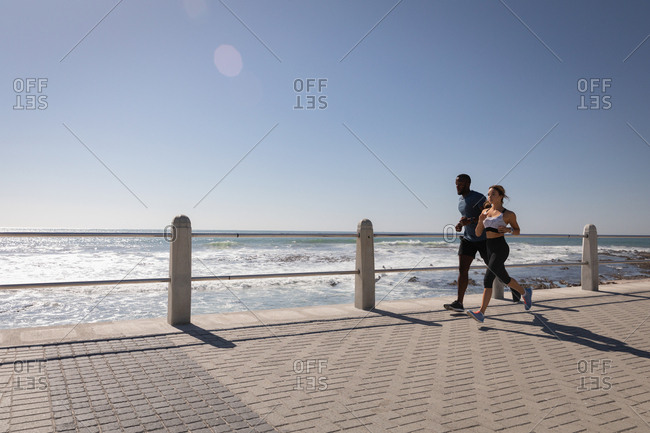 Side view of young multi-ethnic couple jogging on pavement at beach promenade