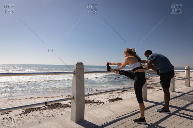 side view of young multi-ethnic couple exercising near beach on promenade
