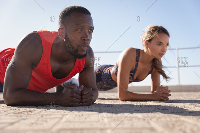 Side view of young multi-ethnic couple doing planking exercises on pavement