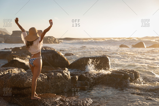 Rear view of beautiful Caucasian woman standing with open arm at beach on a sunny day