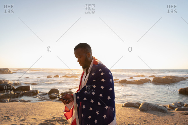 Side view of young African-American man wrapped American flag while using mobile phone on the beach at sunset