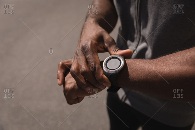 Mid section of African-American man looking at smart watch on street. He sets his watch