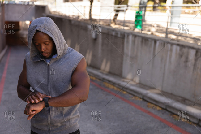 Front view of young African-American man looking at smart watch on street. Setting his swatch