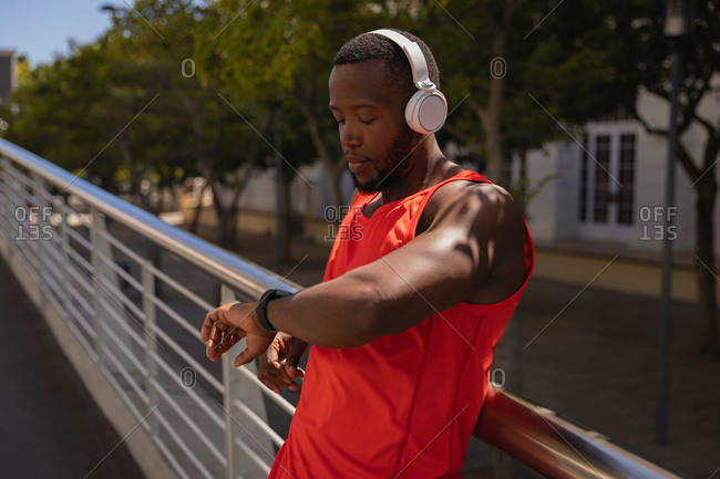 Side view of young African-American fit man with headset looking at smart watch while standing by railing