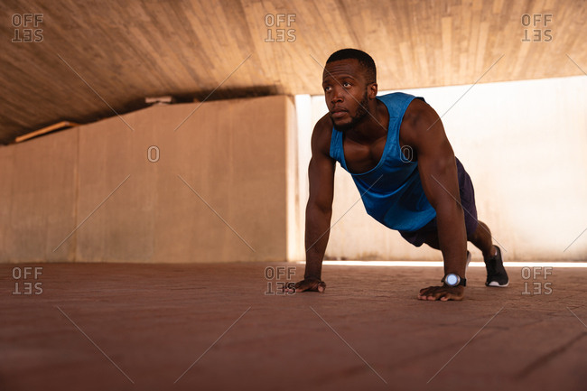 Low angle view of young African-American fit man doing push-up exercise under the bridge