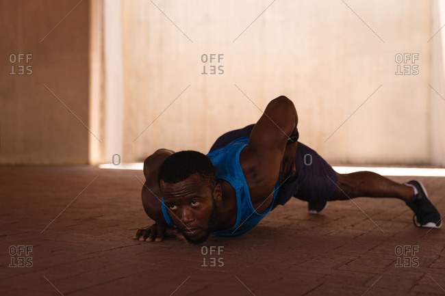 Front view of young African-American fit man doing one-arm push-up exercise under the bridge on a sunny day