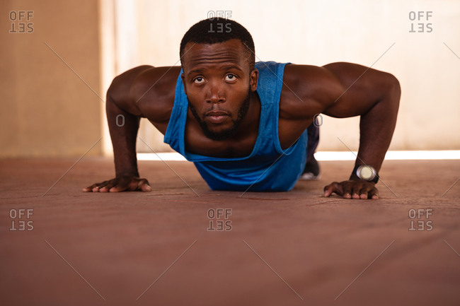 Portrait of young African-American fit man doing push-up exercise under the bridge