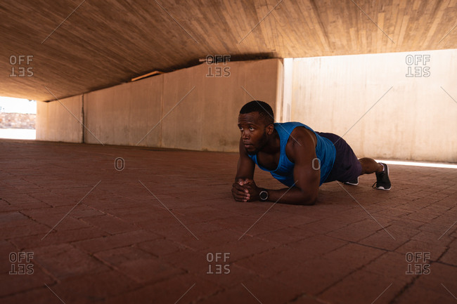 Side view of young African-American fit man doing plank exercise under the bridge on a sunny day