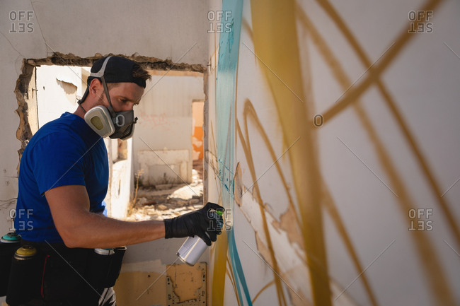 Side view of young Caucasian graffiti artist spray painting weathered wall room
