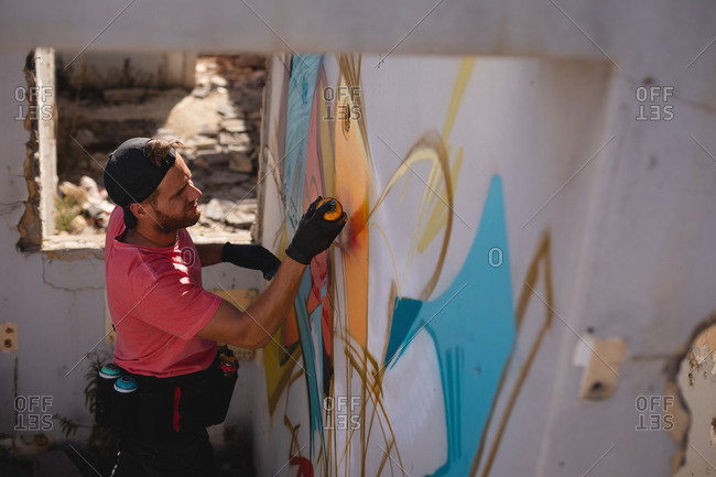 High angle view of young Caucasian graffiti artist spray painting on weathered wall room