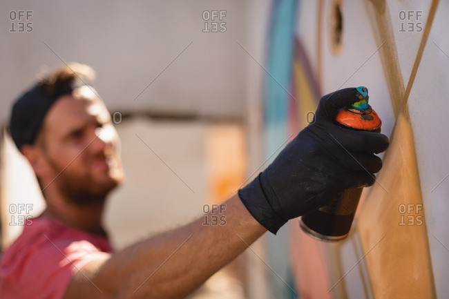 Side view of young Caucasian graffiti artist spray painting on weathered wall room