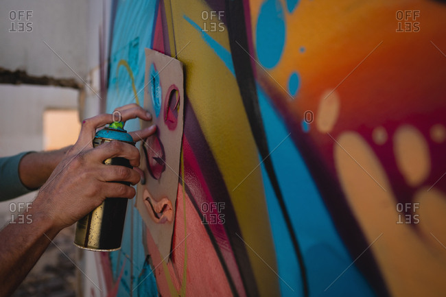 Side view of young Caucasian graffiti artist spray painting on card board at alley