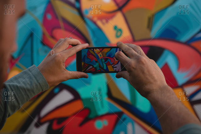 Rear view of young Caucasian graffiti artist capturing photo of painted wall