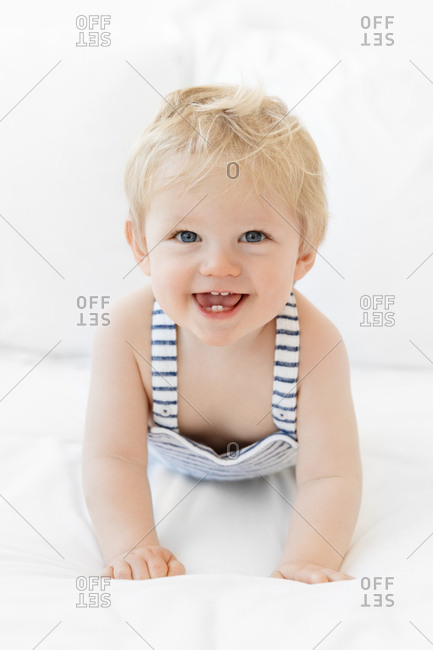 Portrait of a cute baby with blonde hair and blue eyes crawling on bed