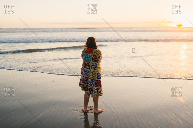 Girl wrapped in a blanket watching sunset over the ocean