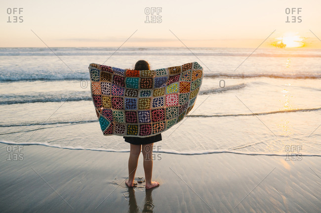 Girl holding a blanket watching sunset over the ocean
