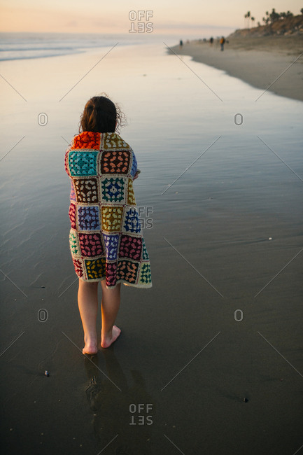 Girl wrapped in a blanket walking on beach at sunset