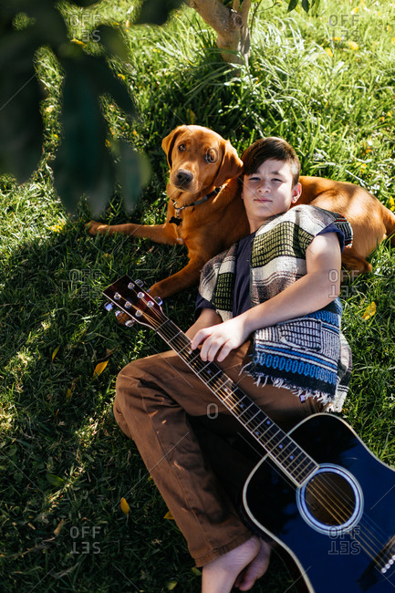 Boy holding guitar lying on his dog in the grass