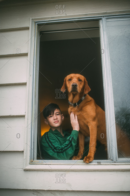 Boy with his dog in an open window