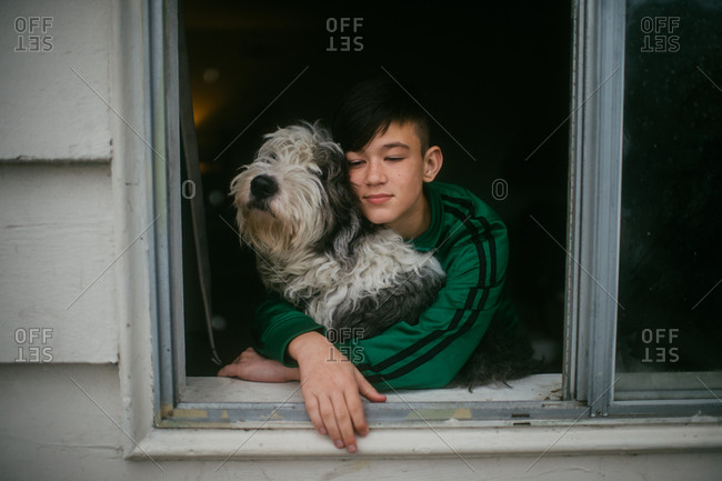 Boy hugging shaggy dog and looking out the window