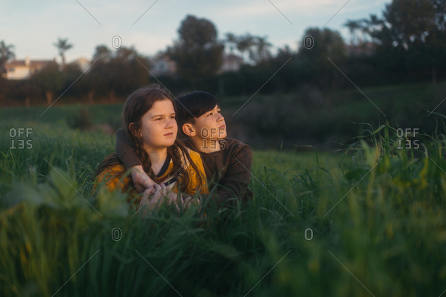 Brother and sister sitting in tall grass watching sunset together