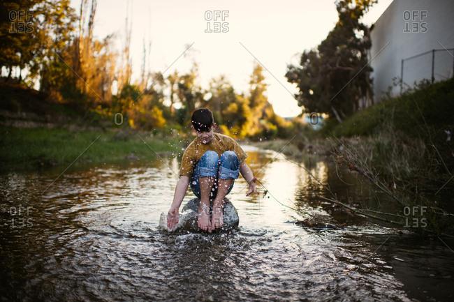Boy sitting on rock in river splashing water