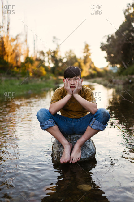 Boy sitting barefoot on rock in a stream with head resting in his hands