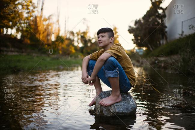 Boy sitting barefoot on rock in a stream