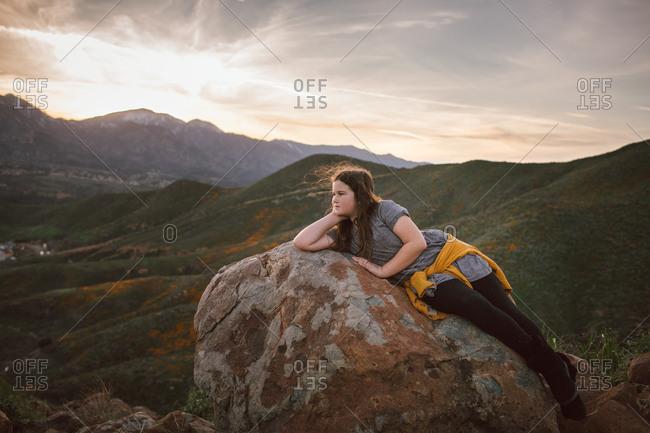 Girl lying on rock overlooking California mountains