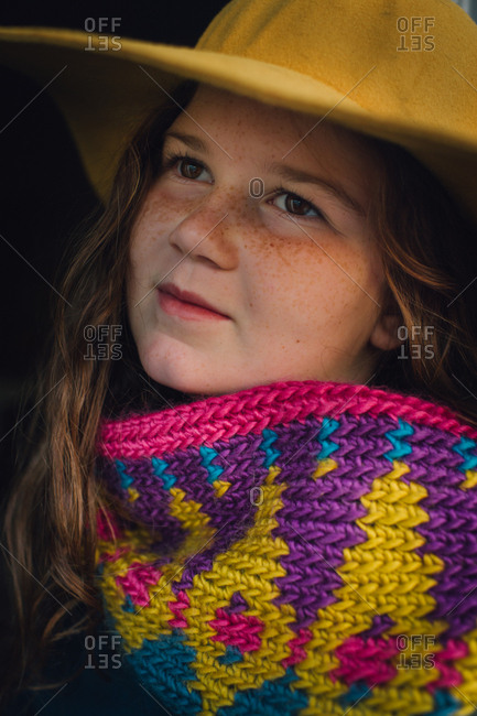 Portrait of a young girl with freckles wearing a colorful scarf and hat