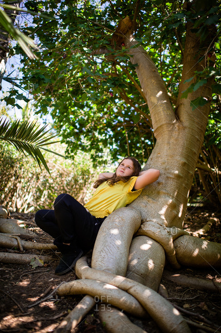 Girl lying back relaxing on a tree