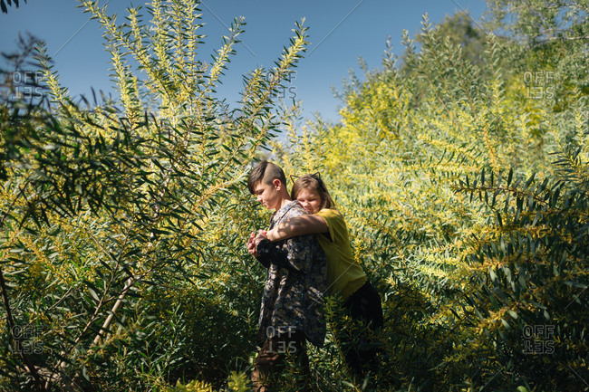 Sister hugging her brother surrounded by acacia trees