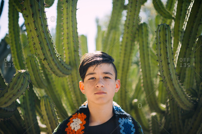 Boy standing by cactus plant