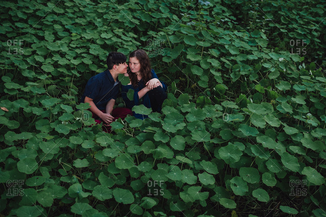 Brother and sister sitting face to face in a field of green leaves