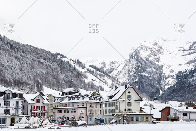 Switzerland - December 9, 2017: Buildings in a town covered in snow in the Swiss Alps