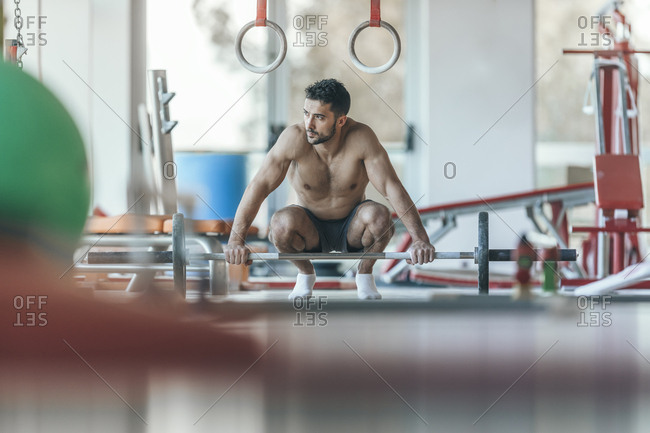 Gymnast rests after weight exercise with a barbell