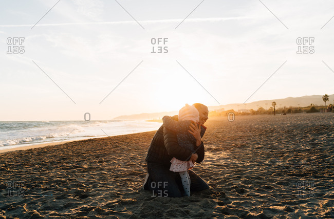 Father and daughter hugging on the beach in winter