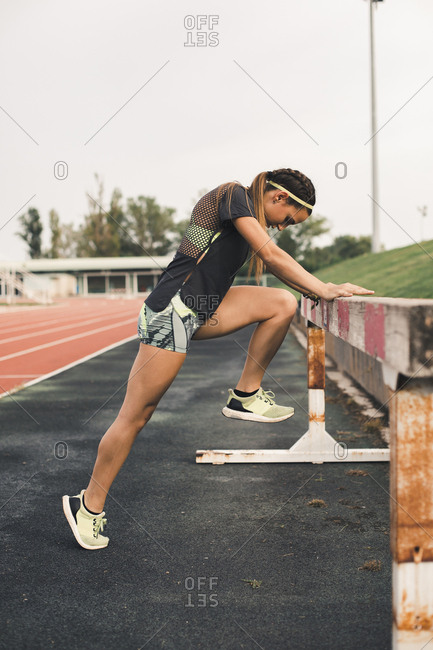 Female athlete doing warm-up exercises on tartan track