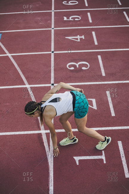 Top view of female runner in starting position on tartan track