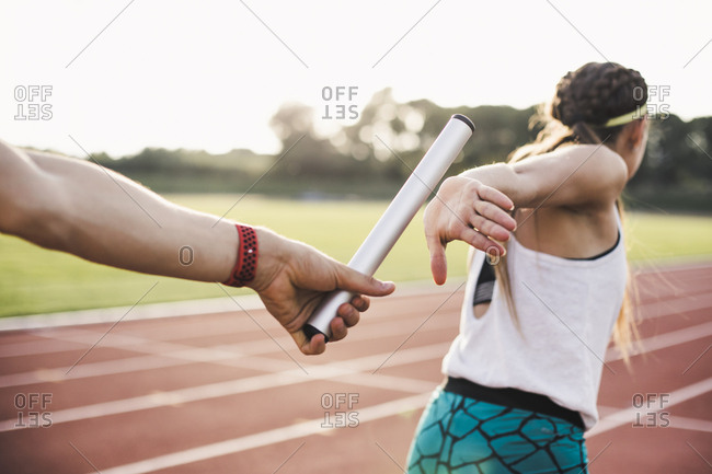 Close-up of a athlete passing the baton to a female athlete