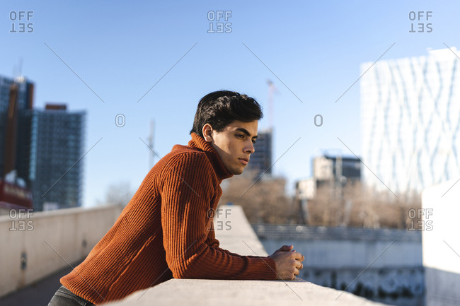 Fashionable young man wearing turtleneck pullover leaning on a wall looking at distance
