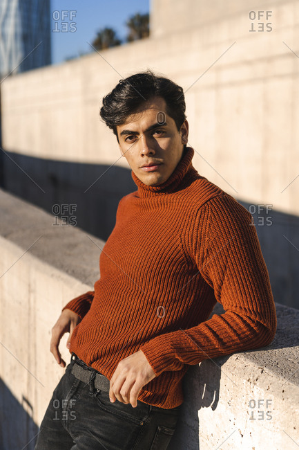 Portrait of fashionable young man wearing turtleneck pullover leaning on a wall at sunlight