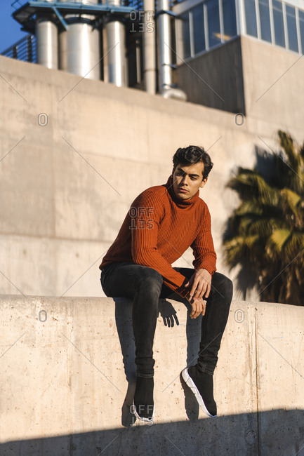Portrait of fashionable young man wearing turtleneck pullover sitting on a wall at sunlight