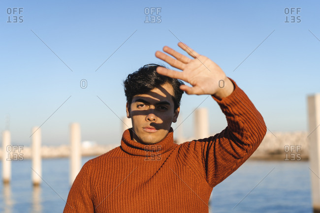 Portrait of young man wearing turtleneck pullover raising his hand