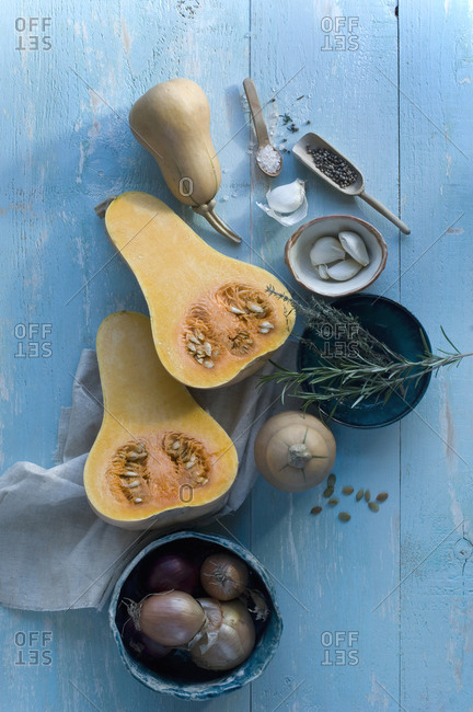 Whole and sliced butternut squash- garlic cloves and herbs on light blue wood