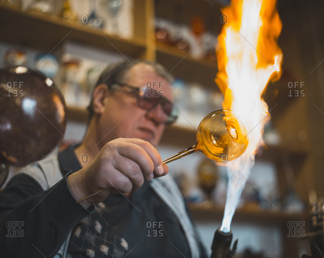 Glass blower forming melting glass