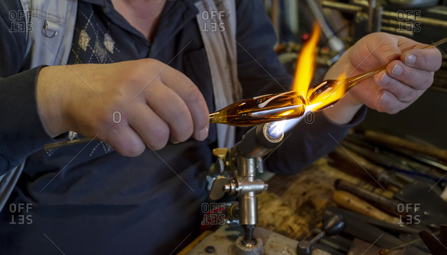Hands of glass blower forming melting glass