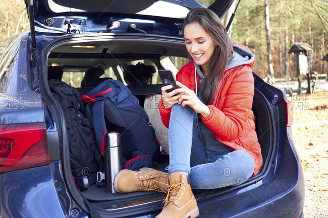 Woman using smartphone while sitting in car trunk during road trip