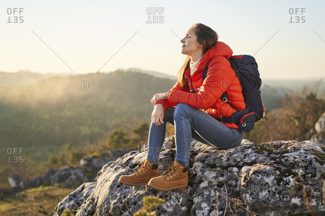 Woman on a hiking trip in the mountains resting on a rock